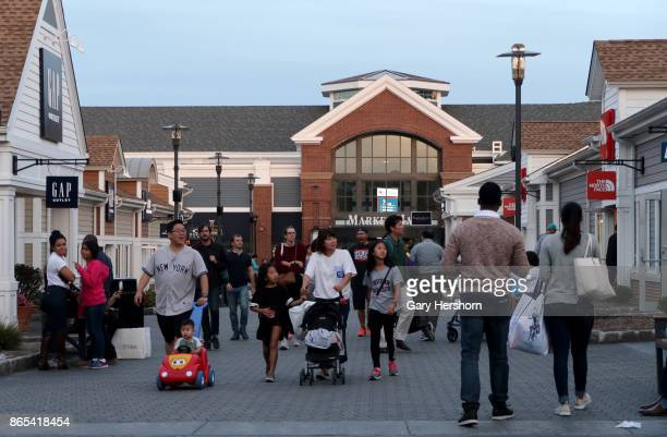 People walk past the Gap Outlet and The North Face stores the Woodbury Common Premium Outlets Mall on October 21 2017 in Central Valley NY