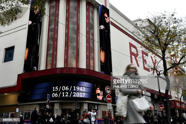 People walk past the Grand Rex cinema bearing on its facade and the date of birth and death of late French singer and actor Johnny Hallyday on...