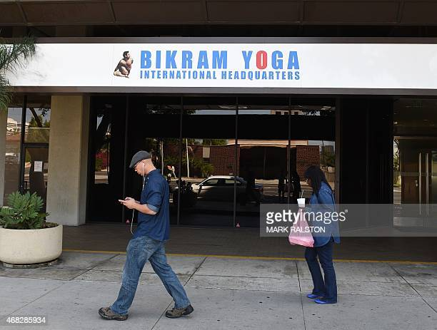 People walk past the headquarters of Bikram Yoga in Los Angeles California on April 1 2015 Yoga guru Bikram Choudhury faces six civil lawsuits from...
