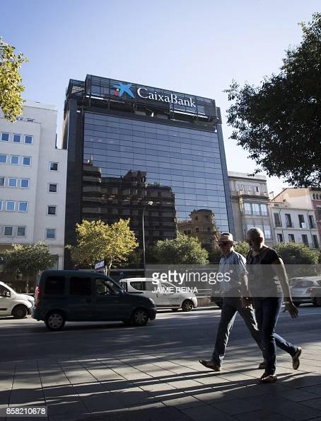 People walk past the headquarters of Catalan bank 'La Caixa