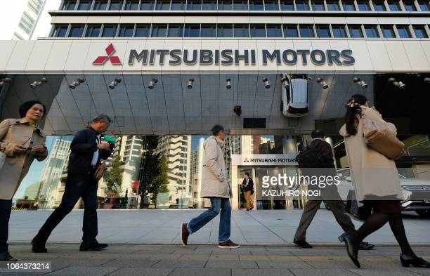 People walk past the headquarters of Mitsubishi Motors in Tokyo on November 23 2018 Nissan's board sacked Carlos Ghosn as chairman on November 22 a...