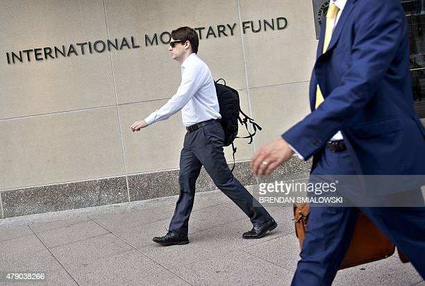 People walk past the headquarters of the International Monetary Fund June 30 2015 in Washington DC Greece confirmed it would fail to make a key IMF...