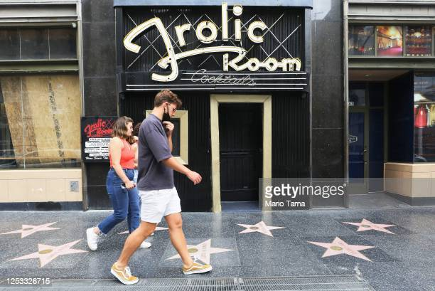 People walk past the historic Frolic Room bar which is shuttered along Hollywood Boulevard amid the COVID-19 pandemic on June 29, 2020 in Los...