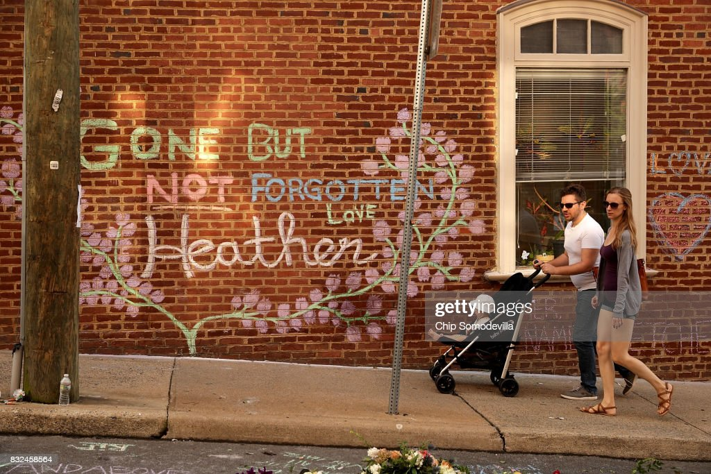 People walk past the informal memorial set up at the site where Heather Heyer was killed and 19 others injured when a car slamed into a crowd of people protesting against a white supremacist rally August 16, 2017 in Charlottesville, Virginia. Charlottesville will hold a memorial service for Heyer Wednesday, four days after she was killed when a participant in a white nationalists, neo-Nazi rally allegedly drove his car into the crowd of people demonstrating against the 'alt-right' gathering.