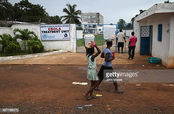 People walk past the Island Clinic Ebola treatment center on October 13 2014 in Monrovia Liberia A planned strike was averted as most nurses and...