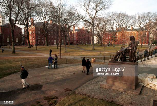 People walk past the John Harvard statue at Harvard University''s main campus December 19 2000 in Cambridge MA Members of a committee searching for a...