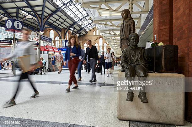 People walk past the Kindertransport memorial monument at Liverpool street station in London on July 2 2015 Nicholas Winton a Briton who saved...