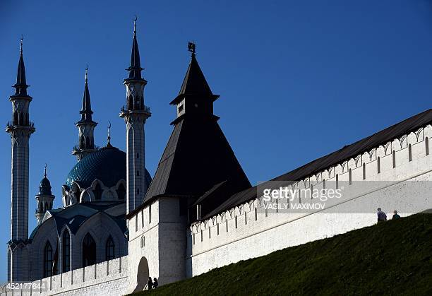 People walk past the Kremlin in Kazan the capital of Russia's Muslim autonomic republic of Tatarstan on July 14 with Kul Sharif mosque seen behind...