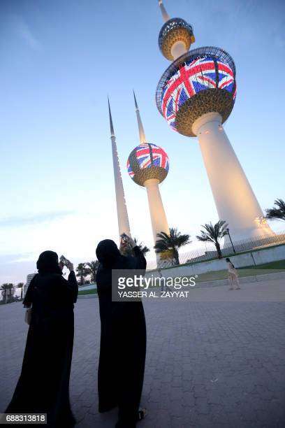 People walk past the Kuwait Towers as they are illuminated with the colours of the United Kingdom flag in tribute to the victims of the May 22 terror...
