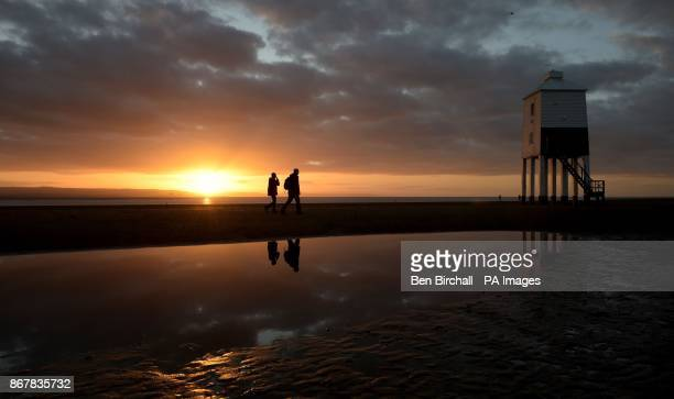 People walk past the lighthouse at BurnhamonSea Somerset as the sun sets an hour earlier after the clocks went back one hour last night due to the...