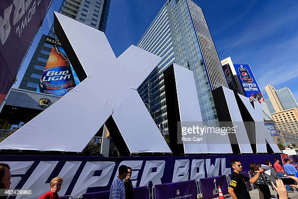 People walk past the logo for the upcoming Super Bowl XLIX between the Seattle Seahawks and New England Patriots in an NFL fan on January 28 2015 in...
