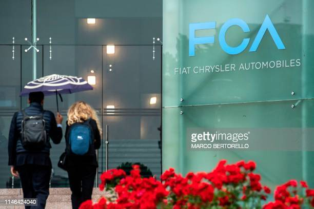 People walk past the logo of Fiat Chrysler Automobiles at the Fiat Mirafiori car plant on May 27 2019 in Turin northern Italy French and ItalianUS...