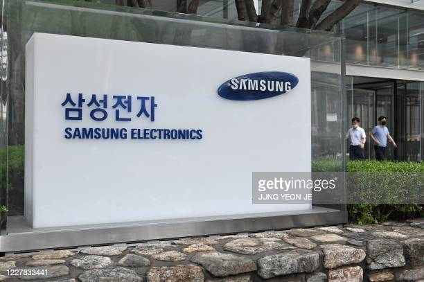 People walk past the logo of Samsung Electronics at the company's Seocho building in Seoul on July 30, 2020. - Samsung Electronics reported on July...