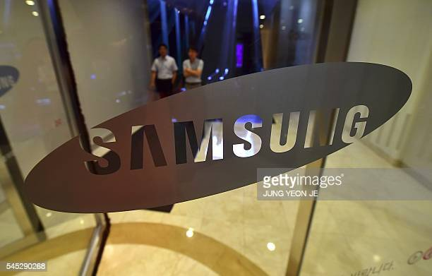 People walk past the logo of Samsung Electronics at the company's headquarters in Seoul on July 7 2016 Samsung Electronics on July 7 flagged its...