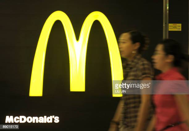 People walk past the logo of US fastfood giant McDonald's in Beijing on July 14 2009 Top Chinese and US leaders have agreed to meet in late July in...