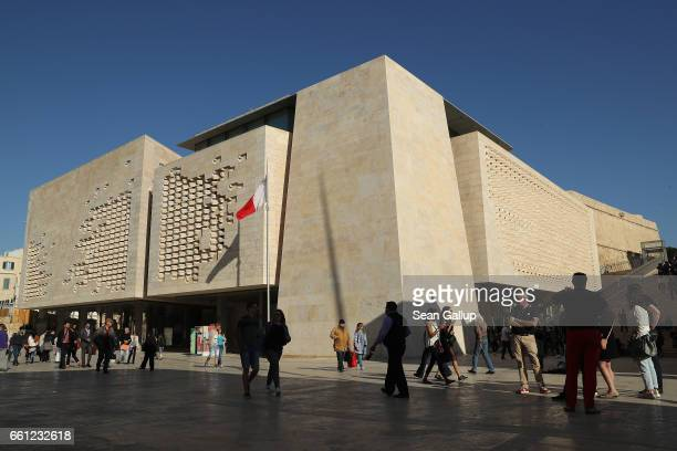 People walk past the Maltese Parliament building on March 30 2017 in Valletta Malta Valletta a fortfied town that dates back to the 16th century is...