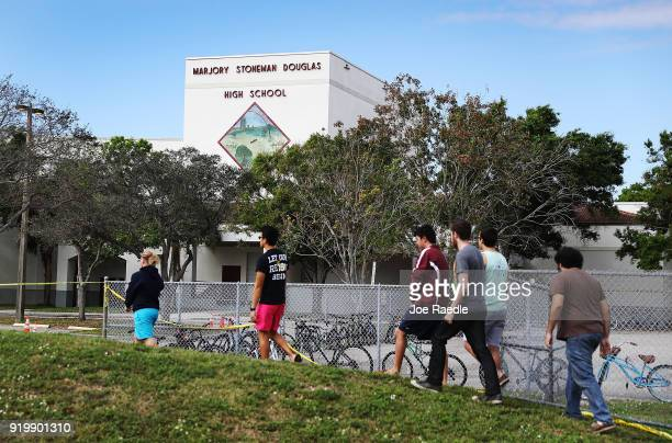 People walk past the Marjory Stoneman Douglas High School on February 18 2018 in Parkland Florida Police arrested 19 year old former student Nikolas...