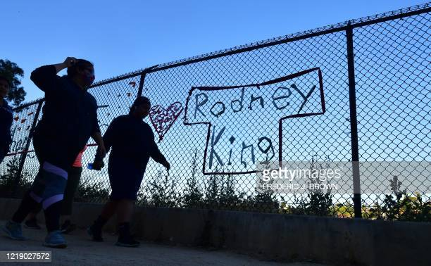 People walk past the name Rodney King seen on a chain-link fence surrounding Silver Lake Reservoir in Los Angeles, on June 9 where a new art...