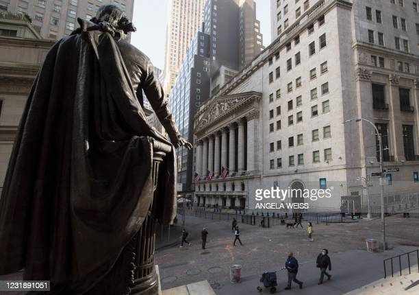 People walk past the New York Stock Exchange and a statue of George Washington at Wall Street on March 23, 2021 in New York City. - Wall Street...