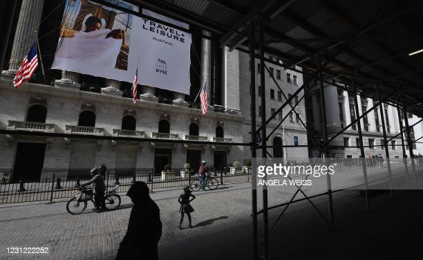 People walk past the New York Stock Exchange at Wall Street on February 17, 2021 in New York City.