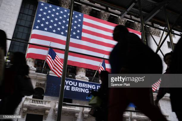 People walk past the New York Stock Exchange on February 12 2020 in New York City The market closed up over 250 points as gains in tech companies and...
