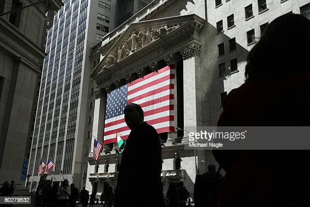 People walk past the New York Stock Exchange on March 17 2008 in New York City Stocks are volatile on Wall Street following news of JP Morgan Chase...