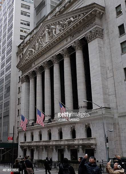 People walk past the New York Stock Exchange on the Wall Street in New York on January 20 2105 US stocks finished with modest gains on January 20...