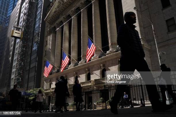 People walk past the New York Stock Exchange on Tuesday afternoon, October 23, 2018 in New York City. Following a 500 point drop earlier in the day...