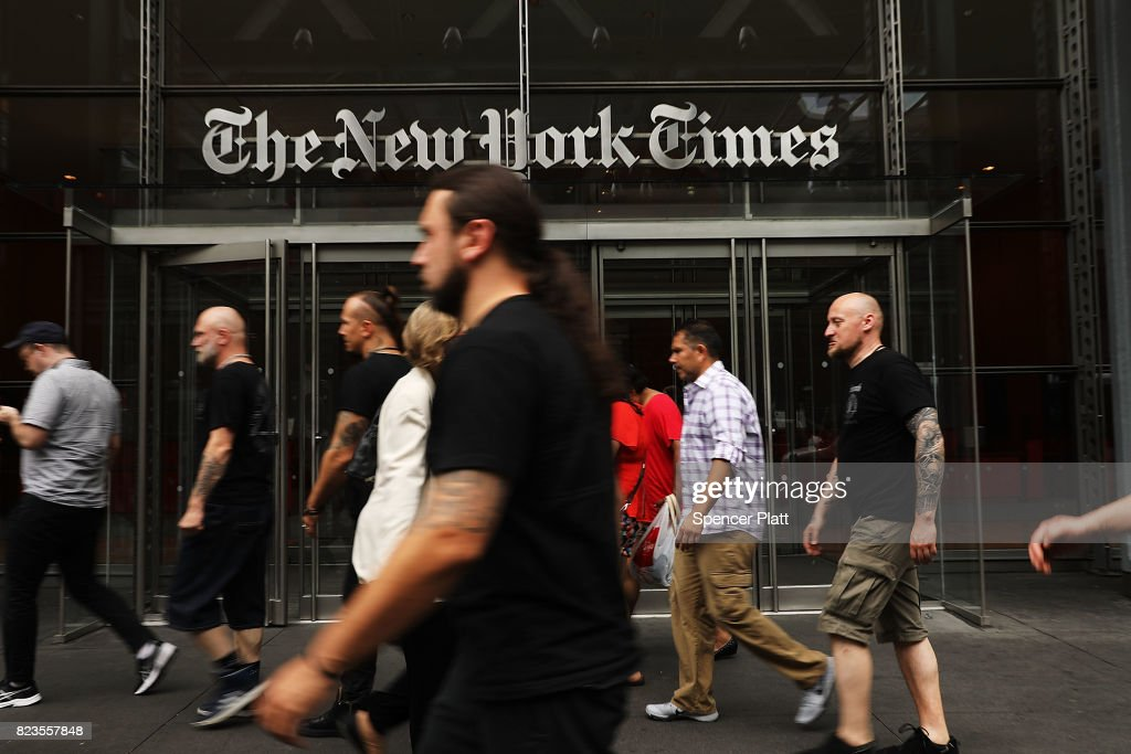 People walk past the New York Times building on July 27, 2017 in New York City. The New York Times Company shares have surged to a nine-year high after posting strong earnings on Thursday. Partly due to new digital subscriptions following the election of Donald Trump as president, the company reported a profit of $27.7 million in the second quarter, up from $9.1 million in the same period last year.