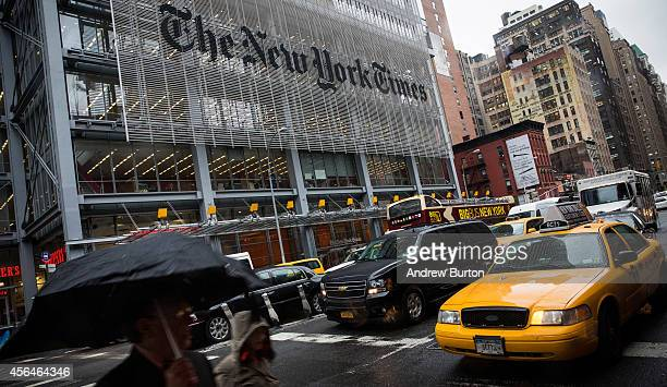 People walk past The New York Times building on October 1 2014 in New York City The Times announced plans to cut approximately 100 jobs from the...