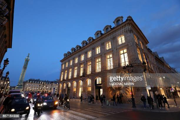People walk past the newly opened Louis Vuitton flagship store off Place Vendome in Paris on October 3 2017