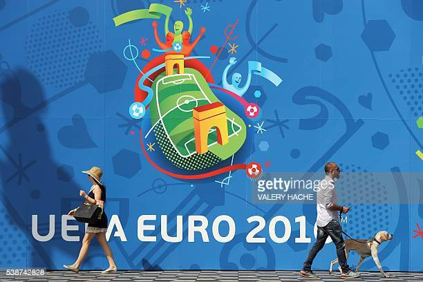 TOPSHOT People walk past the Nice fan zone banner in Nice southeastern France on June 8 ahead of the UEFA EURO 2016 football championships that takes...