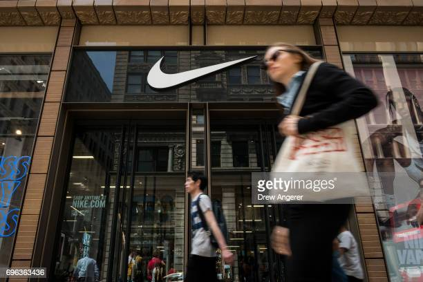 People walk past the Nike SoHo store June 15 2017 in New York City Nike announced plans on Thursday to cut about 2 percent of its global workforce