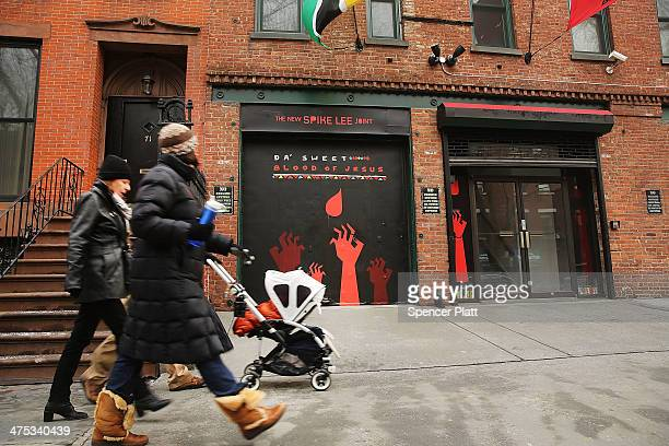 People walk past the offices of director and artist Spike Lee in the Fort Greene neighborhood February 27, 2014 in the Brooklyn borough of New York...