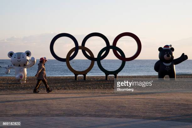 People walk past the Olympic rings and statues of the 2018 PyeongChang Winter Olympic Games mascot Soohorang left and Bandabi right at Gyeongpo beach...