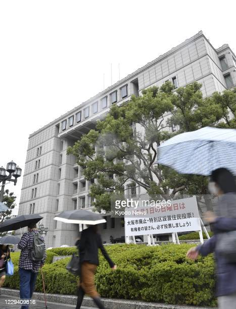 People walk past the Osaka city office on Nov. 2 a day after voters opposed reorganizing the western Japan city into a metropolis akin to Tokyo by a...