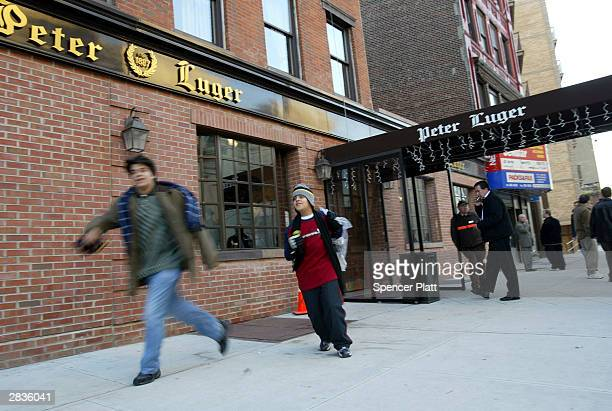 People walk past the Peter Luger steakhouse December 29, 2003 in New York City. U.S. Officials on December 28 insisted there was no risk to consumers...