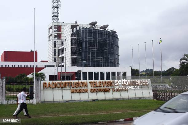 People walk past the premises of the National Radio and Television centre in Libreville on June 16 after unknown assailants targeted several medias...