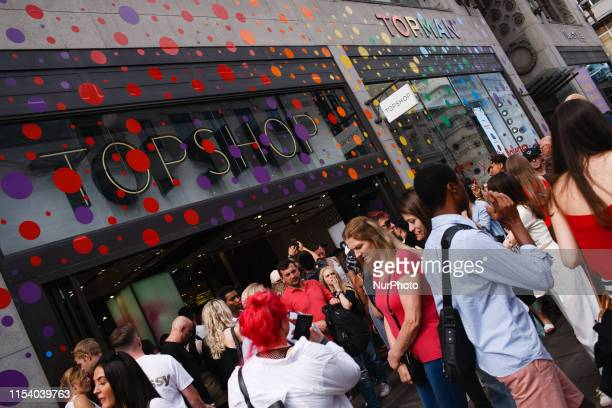 People walk past the Pride-themed, rainbow-decorated facade of clothing retailer Topshop on Oxford Street in London, England, on July 5, 2019....