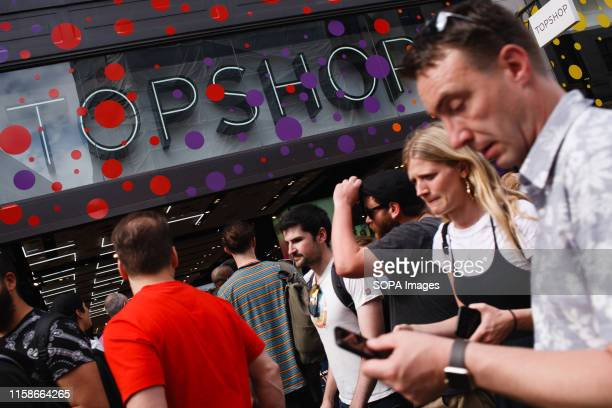 People walk past the Pride-themed, rainbow-decorated facade of clothing retailer Topshop on Oxford Street in London. This year marks the 50th...
