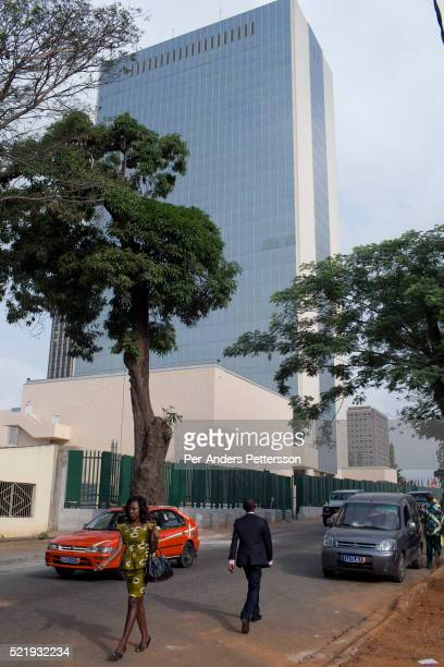 People walk past the provisional headquarters of the African Development Bank in Abidjan Ivory Coast The Bank moved to Tunisia over 10 years ago due...