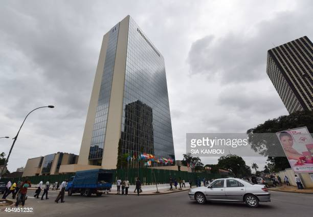 People walk past the provisional headquarters of the African Development Bank on September 8 2014 in Abidjan after a ceremony marking the effective...
