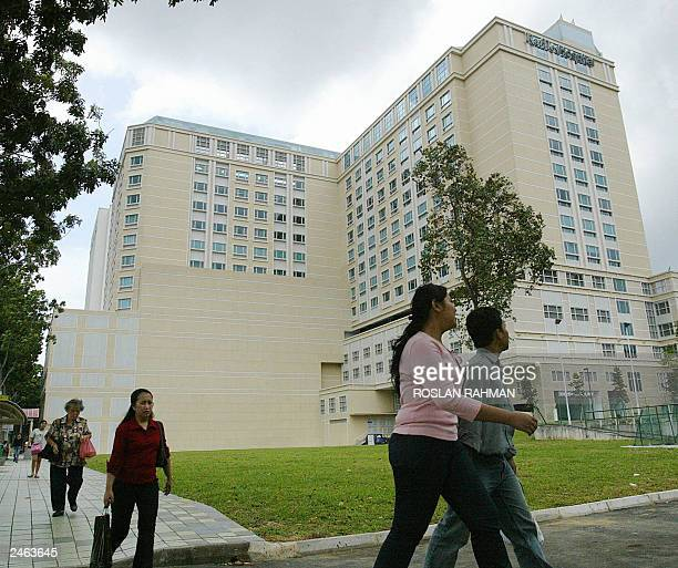 People walk past the Raffles Hospital where the Iranian twin sisters Laden and Laleh Bijani undergoing separation operation in Singapore 07 July 2003...