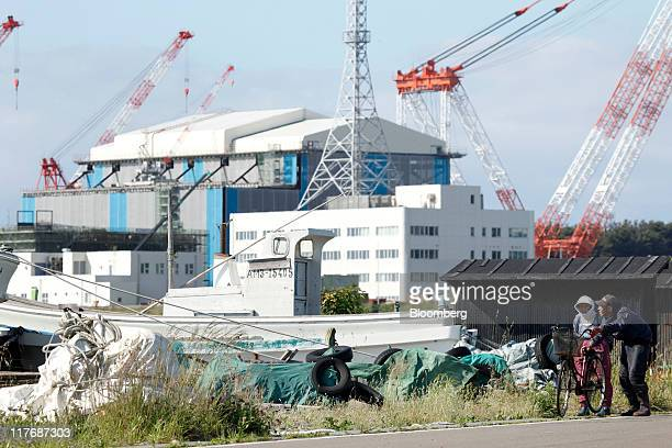 People walk past the reactor building for Electric Power Development Co.'s Oma nuclear power plant, under construction, in Oma Town, Aomori...