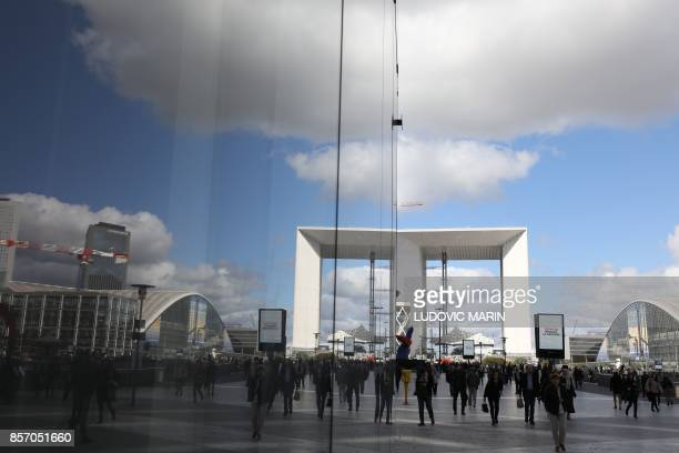 People walk past the reflection of the Big Arche building in the La Defense business district in Courbevoie on October 3 2017 / AFP PHOTO / LUDOVIC...