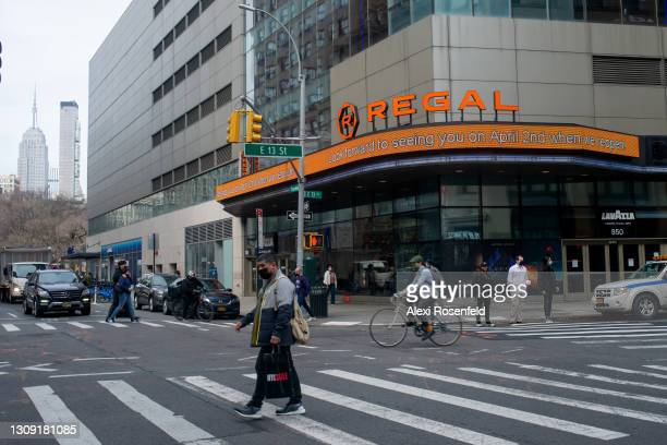 """People walk past the Regal Cinemas marquee that reads, """"look forward to seeing you on April 2nd when we reopen!"""" at the Regal cinemas in Union Square..."""