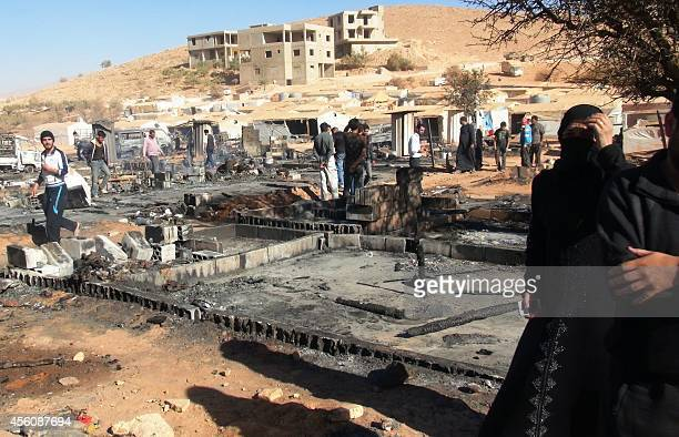 People walk past the remains of burnt tents at a Syrian refugee camp in Arsal in eastern Lebanon on September 25 a few hours after a raid by the...