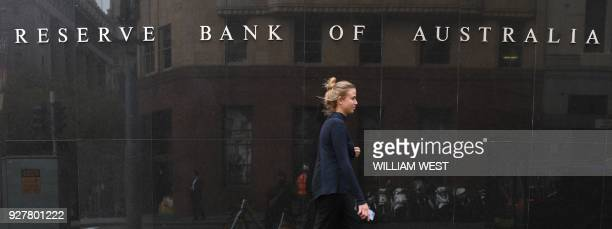 People walk past the Reserve Bank of Australia building in Sydney on March 6 as Australia's central bank kept interest rates at a record in a widely...