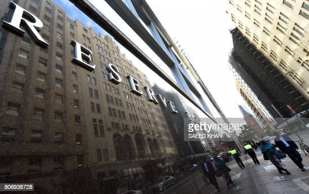 People walk past the Reserve Bank of Australia building in the central business district of Sydney on July 4 2017 Australia's central bank kept...