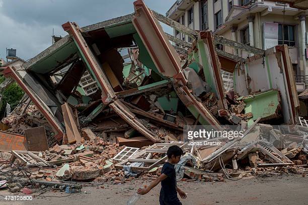 People walk past the rubble following yesterday's earthquake on May 13 2015 in Kathmandu Nepal A 73 magnitude earthquake struck in Nepal only two...